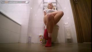 Блондиночка мастурбирует в туалете скрещивая ноги и кончает на самом деле